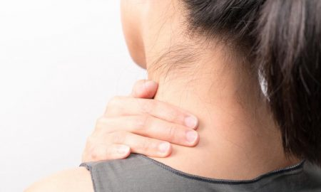 cropped woman holding her neck due to pimple on neck