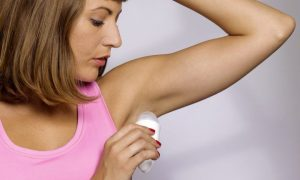 cropped young woman applying underarm deodorant  cfcefbcb